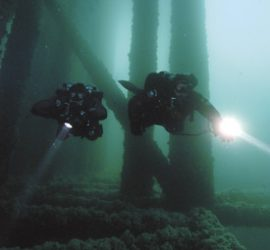 two properly weighted divers float between the legs of a pier