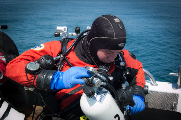 diver loads a decompression stage cylinder before a dive